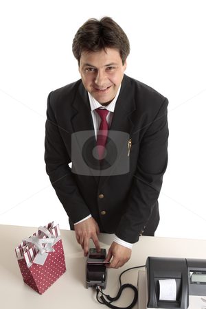 Man buys Christmas present credit card stock photo, A man dressed in suit buying a birthday, Christmas or special occasion present using credit or debit card. by Leah-Anne Thompson