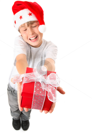 Joy of Giving a  Christmas Gift stock photo, A happy child hands up a present wrapped with silver gauze ribbon in the spirit of Christmas. Selective focus to the gift only.  Boy is not in focus. by Leah-Anne Thompson