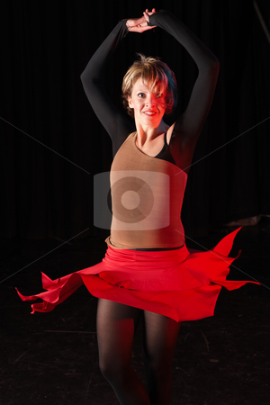 Dancers on stage stock photo, Single Caucasian female freestyle hip-hop dancer in a dancing training session. Lit with spotlights. Movement on edges of dancer by Sean Nel