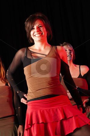 Dancers on stage stock photo, A young adult dancer in front of a group of female freestyle hip-hop dancers in a dancing training session. Lit with spotlights. by Sean Nel