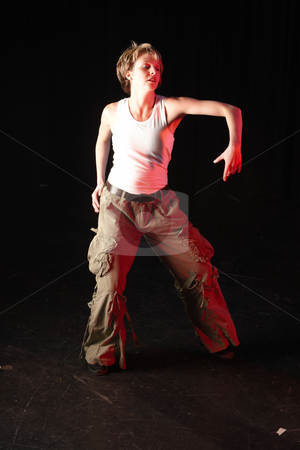 Dancers on stage stock photo, Single Caucasian female freestyle hip-hop dancer in a dancing training session. Lit with spotlights by Sean Nel
