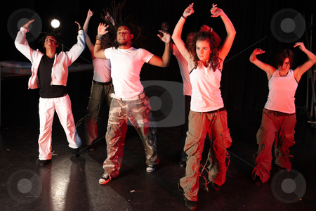 Dancers on stage stock photo, A group of six female and male freestyle hip-hop dancers during dance training session on stage. Lit with spotlights by Sean Nel