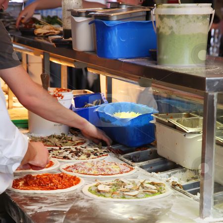 Making Pizza stock photo, Chef Making Assorted Pizzas in a Restaurant by Kheng Ho Toh
