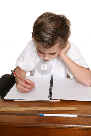 Child doing schoolwork stock photo, A school pupil sitting at desk doing classwork or homework. by Leah-Anne Thompson