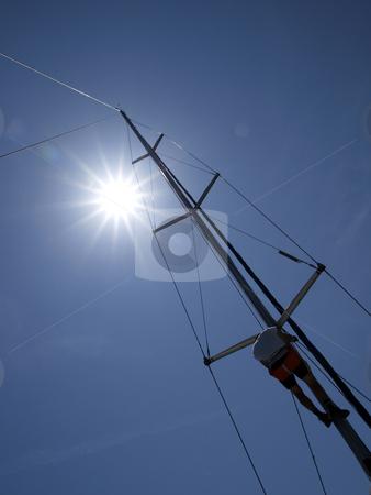 Up to sun stock photo, Sailor climbing hoist by shufu