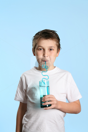 Thirsty boy sipping water from glass stock photo, Thirsty child drinking pure fresh water from a tall glass by Leah-Anne Thompson