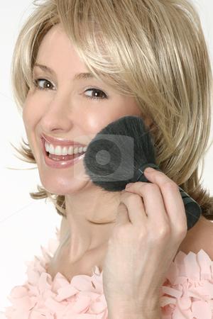 Female holding a large powder brush stock photo, Smiling female holding a large powder brush. by Leah-Anne Thompson