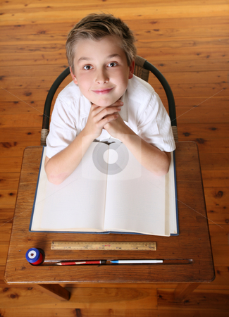 Child at desk with open book stock photo, Confident school boy sitting in class with open book. by Leah-Anne Thompson