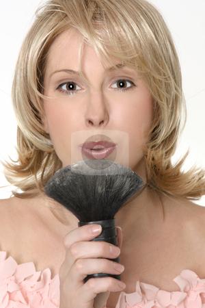 Female flowing excess powder from makeup  brush stock photo, A female blowing gently to remove excess loose powder from a brush. by Leah-Anne Thompson