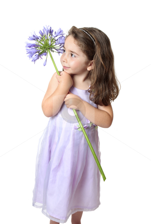 Pretty girl holding a flower stock photo, Pretty young girl in a dress holding a large purple agapanthus. by Leah-Anne Thompson