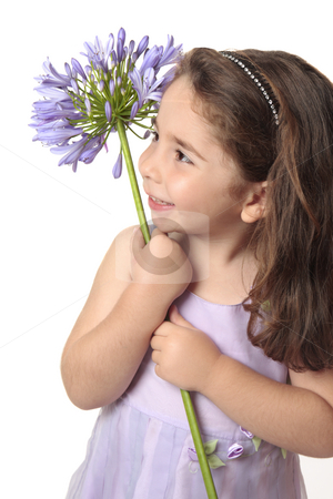 Pretty girl holding a beautiful flower stock photo, Pretty little  girl in purple mauve dress holding a beautiful agapanthus flower and smiling sweetly. by Leah-Anne Thompson