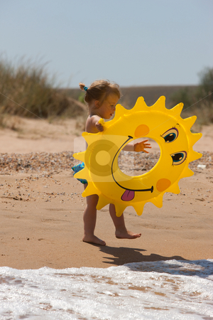 Girl with swimming circle stock photo, People series: little girl  play on the sea beach by Gennady Kravetsky