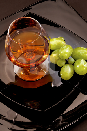 Brandy stock photo, Drink series: glass of cognac grapes on the black plate by Gennady Kravetsky