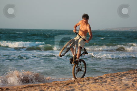 Cyclist stock photo, People series: young man cycle on the beach by Gennady Kravetsky