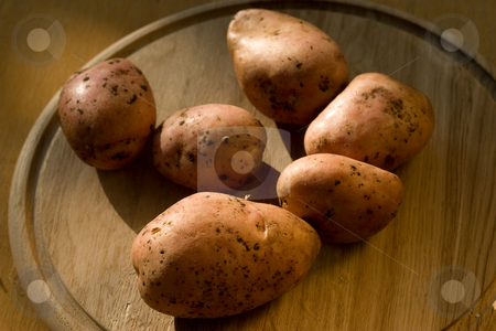 Potatoes stock photo, Food series: some raw potatoeson the wooden board by Gennady Kravetsky
