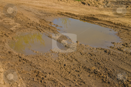 Impassibility of roads stock photo, Ground series: puddle with heavy tires track by Gennady Kravetsky