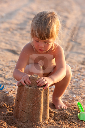 Play  stock photo, People series: little girl on the beach play with sand by Gennady Kravetsky