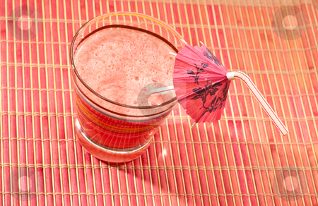 Watermelon drink stock photo, Food series: watermelon drink with umbrella straw on pink napkin by Gennady Kravetsky