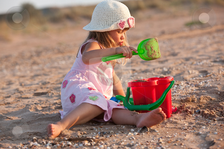 Little girl stock photo, People series: little girl are play the game with sand by Gennady Kravetsky