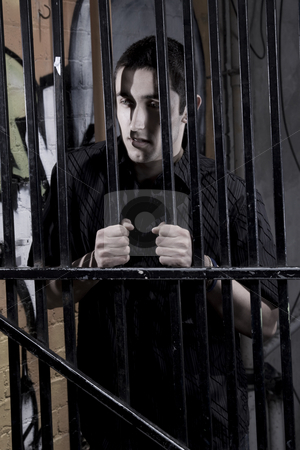 Adolescent stock photo, Young man in an alley behind steel bars by Jandrie Lombard