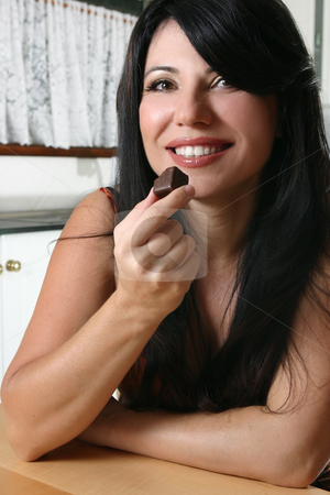 Beautiful woman holding chocolate stock photo, Pretty brunette woman eating a dark chocolate with pleasure by Leah-Anne Thompson