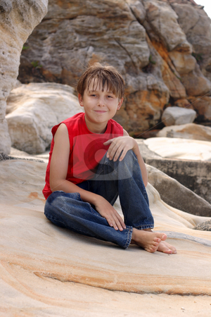Happy child relaxes on rocks stock photo, A happy young boy dressed in denim jeans and tank top, relaxing on some sandstone  rocks by Leah-Anne Thompson