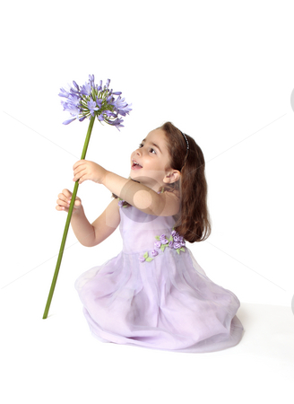 Little girl spinning a large stemmed flower with delight stock photo, A little girl sitting on the floor in pretty mauve dress decorated with floral appliques, is spinning a large stemmed agapanthus lily flower in bloom, with much delight and excitement. by Leah-Anne Thompson