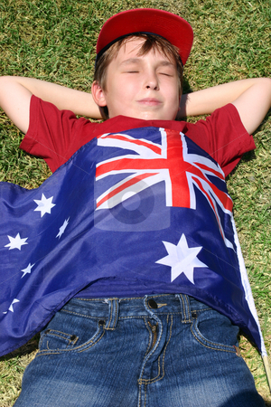 Patriotic boy with flag draped over him stock photo, Patriotic boy with flag draped over him laying in park. by Leah-Anne Thompson