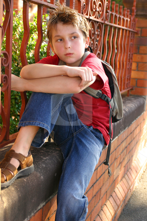 Boy with schoolbag slung over shoulder stock photo, Child sitting on the edge of a brick and wrought iron wall. by Leah-Anne Thompson