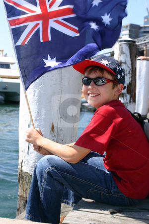 Boy on harbourside pier stock photo, Child relaxing on harbourside wooden pier smiles happily and is waving an Australian flag. by Leah-Anne Thompson
