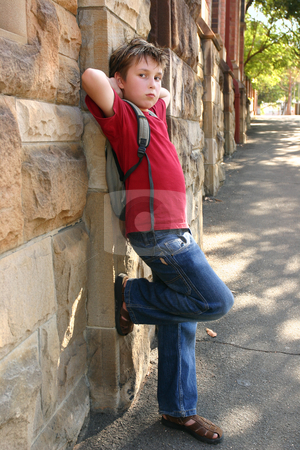 Child leaning against wall stock photo, A child resting against a sandstone brick wall.