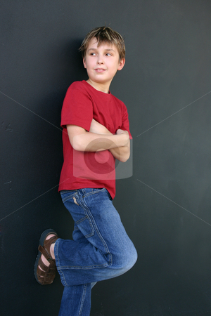 Boy leaning against wall stock photo, Young casually dressed boy leaning against a dark wall. by Leah-Anne Thompson