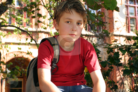 Student waiting outside school stock photo, A school boy waits to be collected from school