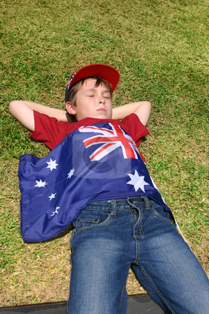 Patriotic boy stock photo, Patriotic Australian boy with Australian flag taking a short rest on grassy area. by Leah-Anne Thompson