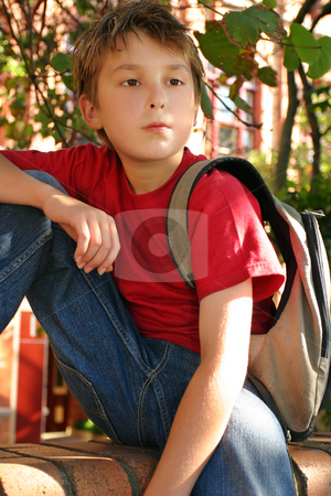Casual student waiting outside school stock photo, Student sitting on brick wall with backpack slung across shoulder, outside school premises. by Leah-Anne Thompson