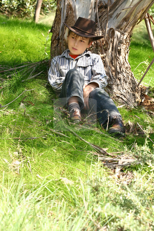 Country boy sitting under a gum tree stock photo, A boy from the bush sits under the shade of an Australian gum tree.  200iso by Leah-Anne Thompson