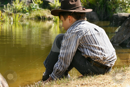 Child sitting by outback billabong stock photo, A child wearing jeans, shirt and hat sits quietly by the edge of a pond by Leah-Anne Thompson