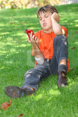 Child sitting in park stock photo, Young child relaxing in the park under the shade of a tree, head titled and looking at the mp3 player in his hand. by Leah-Anne Thompson