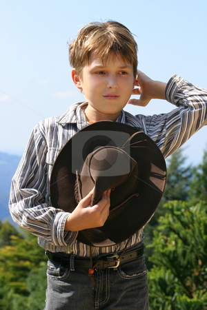 Country farm boy stock photo, Outback rural boy in magnificent high country, holding hat, whilst rustling hair and looking out over the field on a sunny day. by Leah-Anne Thompson
