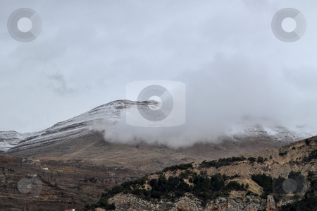 Fog and Mountains stock photo, Mountains covered in snow with fog crossing in between by Tony Abdou