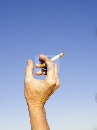 Cigarette stock photo, Smoking a cigarette against a clear blue sky by Mike Smith