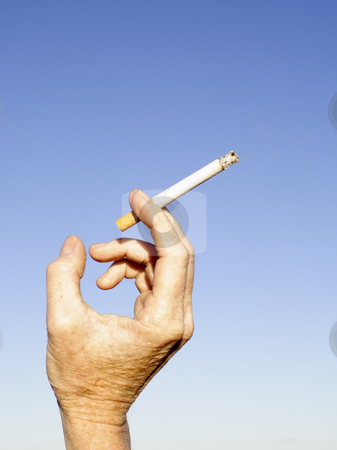 Holding a cigarette stock photo, A hand holding a lighted cigarette against a clear blue sky by Mike Smith