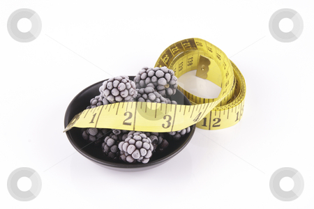 Frozen Blackberries in a Dish with Tape Measure stock photo, Black ripe frozen blackberries in a small round black dish with a tape measure on a reflective white background by Keith Wilson