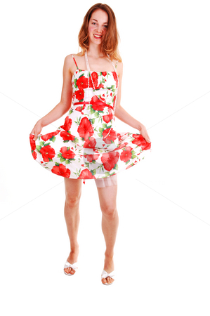 Pretty girl in colorful dress. stock photo, Young, lovely girl in a short colorful dress with brown hair, looking  in the  camera, on high heels, standing in the studio for white background. by Horst Petzold