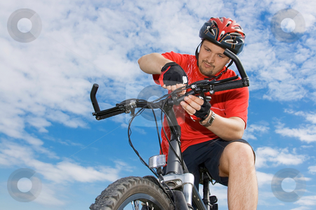 Cyclist fixing his mountain bike his mountain bike stock photo, Portrait of adult cyclist on the mountain bike against blue sky by Tatsiana Amelina