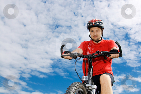 Cyclist on the mountain bike stock photo, Portrait of cyclist on the mountain bike against blue sky by Tatsiana Amelina