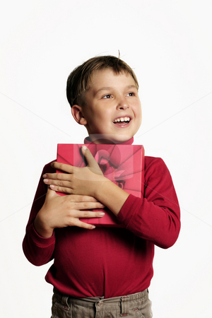 Happy boy holding a present stock photo, Young boy with a red gift box and looking very happy by Leah-Anne Thompson