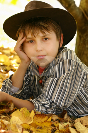 Child in autumn leaves stock photo, A boy from the country laying in a bed of golden yellow foliage under a tree. by Leah-Anne Thompson