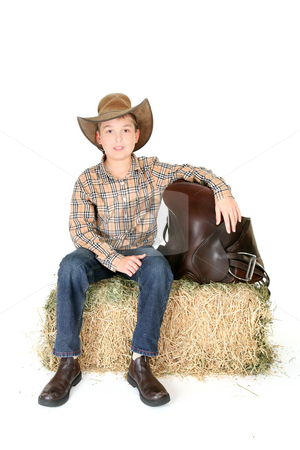 Boy on hay bale with saddle stock photo, Country boy sitting on a hay bale, resting one arm on a leather saddle. by Leah-Anne Thompson