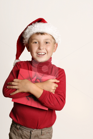 It's Christmas stock photo, An excited  boy in santa hat holding a present by Leah-Anne Thompson